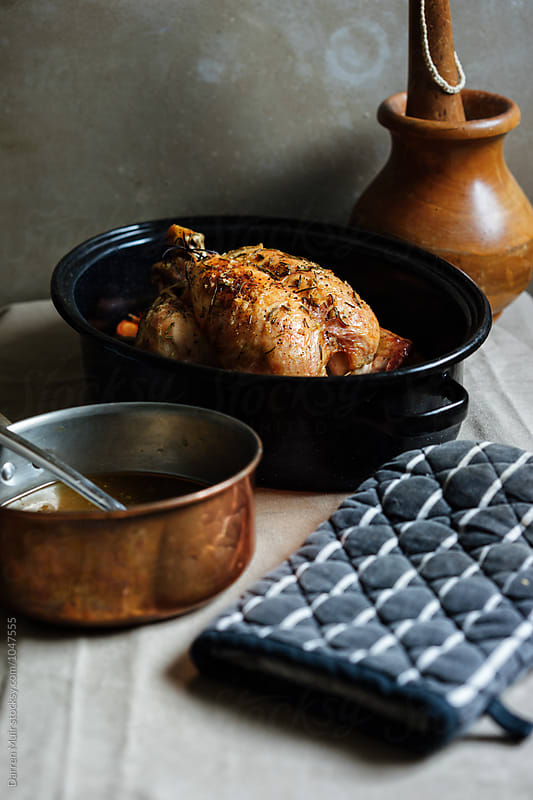 Roast chicken in a roasting tin. by Darren Muir for Stocksy United