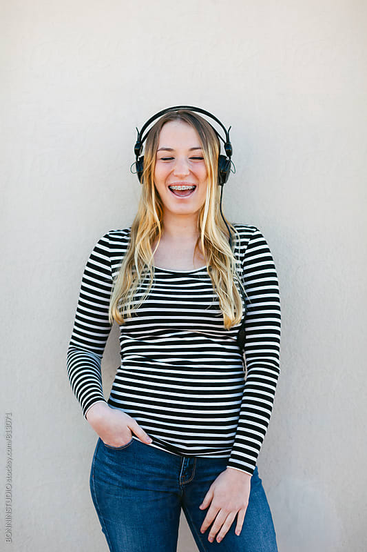 Woman laughing with braces and listening music with headphone. by BONNINSTUDIO for Stocksy United