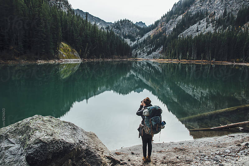 Backpacker takes picture of lake by Tari Gunstone for Stocksy United