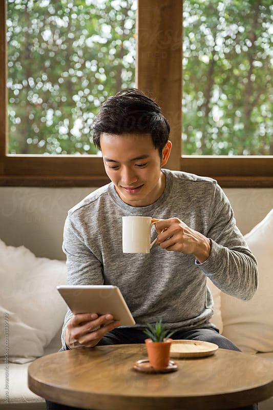 Man drinking cup of coffee and reading news on tablet by Jovo Jovanovic for Stocksy United