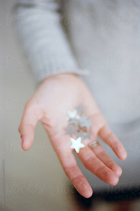 Woman shows sliver stars in her hand by Liubov Burakova for Stocksy United