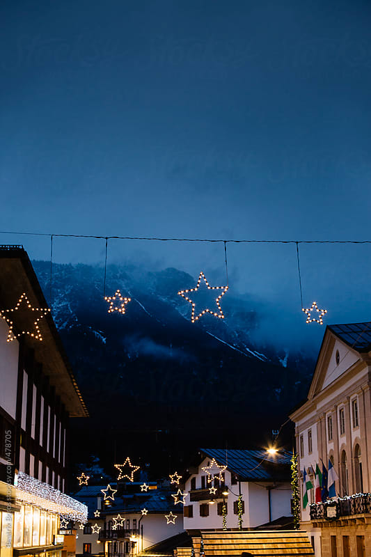 Christmas lights and ornaments on the street by night by Beatrix Boros for Stocksy United