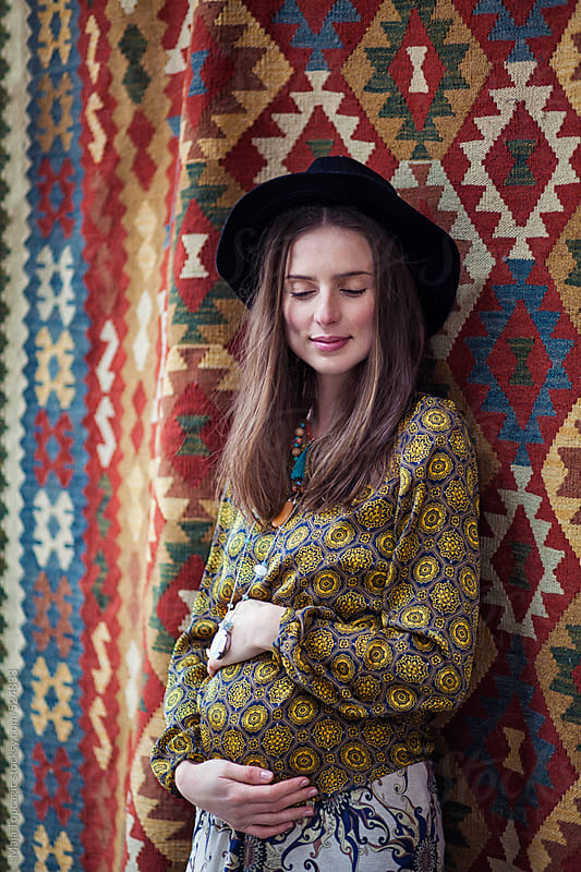 Young beautiful pregnant woman on a pattern background by Maja Topcagic for Stocksy United