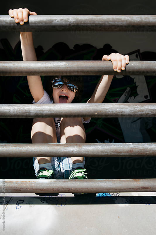 Child wearing sunglasses with his tongue out holding himself by the bars of a window by Beatrix Boros for Stocksy United