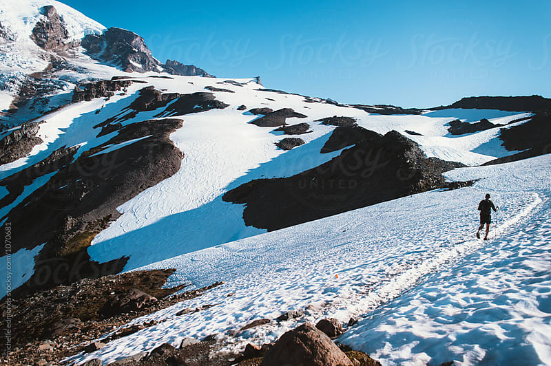 Hiker Crossing a Snowfield on a Trail in Mount Rainier National Park by michelle edmonds for Stocksy United