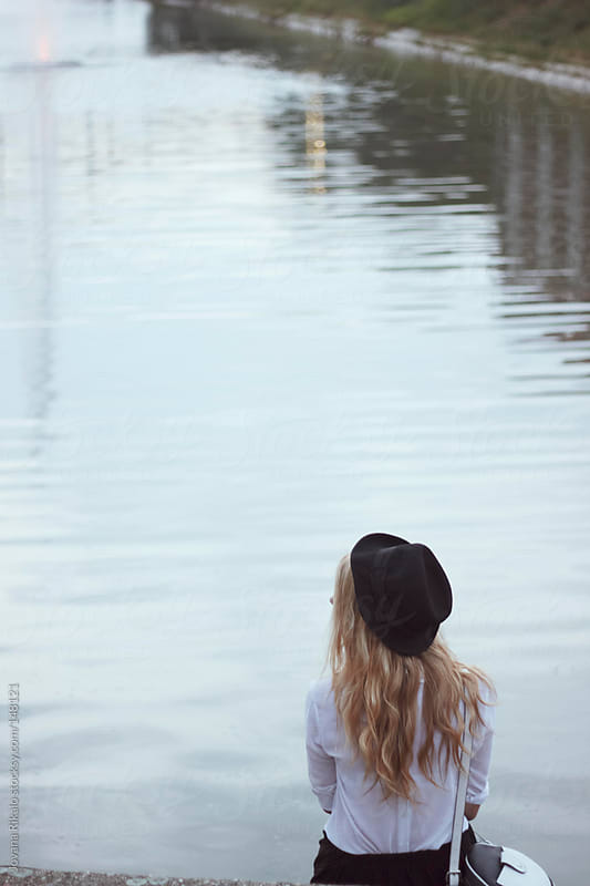 Girl sitting next to river and waiting for a friend by Jovana Rikalo for Stocksy United