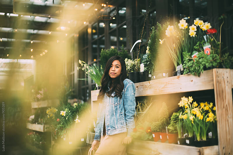 Attractive Young Woman Leaning Against Plant Shelves by Luke Mattson for Stocksy United
