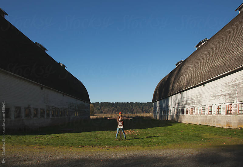 Girl checking out an old barn by Ryan Matthew Smith for Stocksy United