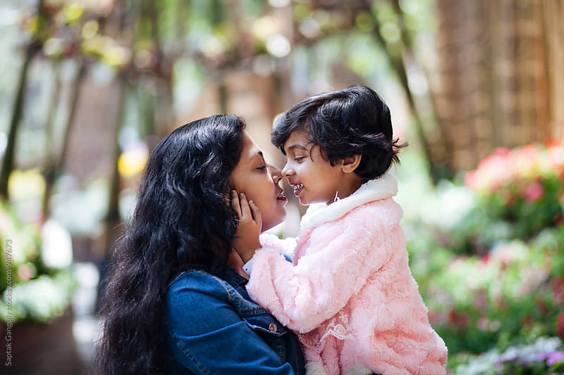 Little girl rub noses with her mother by Saptak Ganguly for Stocksy United