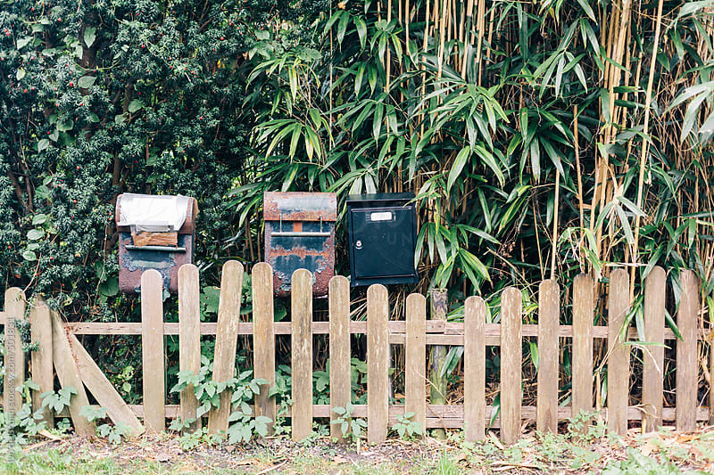 Photo of a  couple of old, worn rusty mailboxes  and a rotten fenche by Ivo de Bruijn for Stocksy United