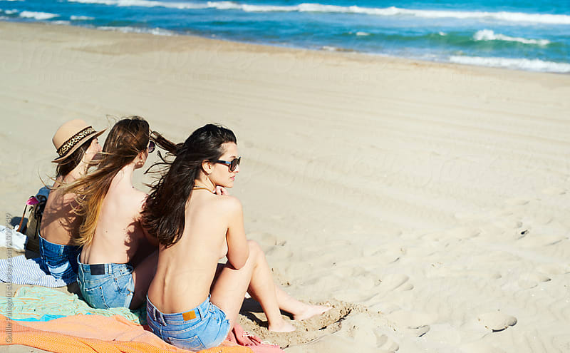 Three topless girls on beach by Guille Faingold for Stocksy United