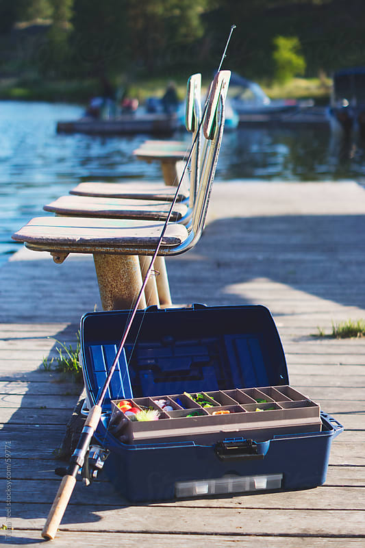 A fishing pole leans against a tackle box next to chairs on a fishing dock by Tana Teel for Stocksy United