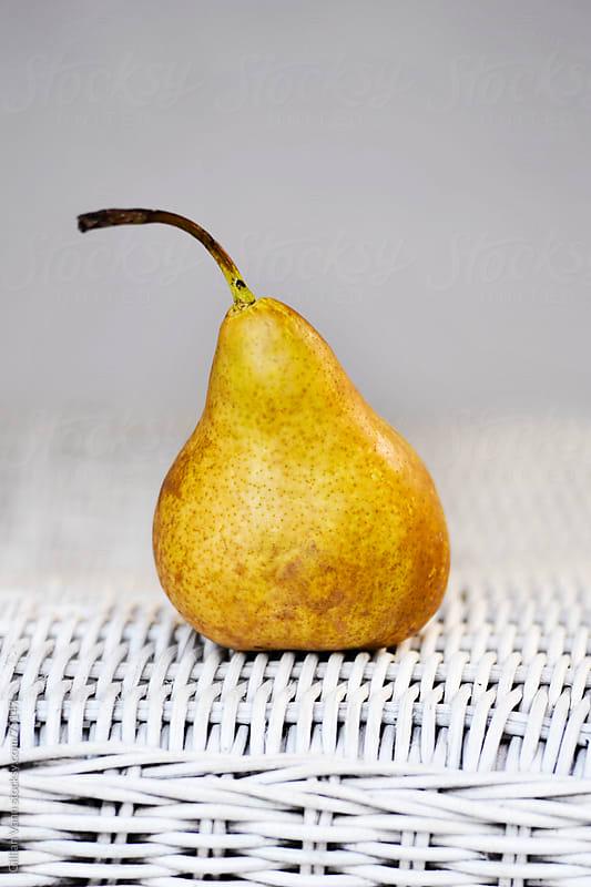 pear on wicker by Gillian Vann for Stocksy United