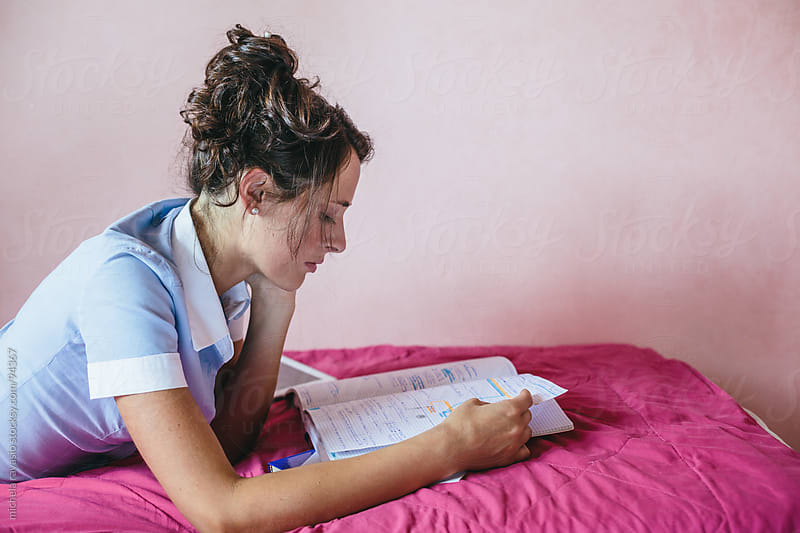 Young woman studying at home by michela ravasio for Stocksy United