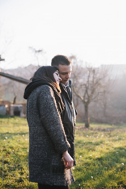 Young couple standing in nature during sunset by Marija Mandic for Stocksy United