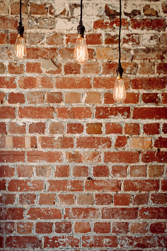 brick wall with 3 hanging pendant lights by Gillian Vann for Stocksy United