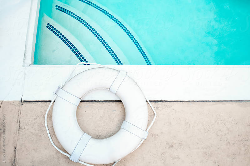 A white life preserver sits on a pool deck next to blue pool by Riley J.B. for Stocksy United