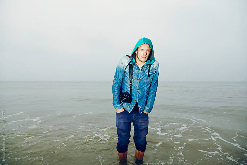 Young man with camera standing in the cold sea by Ivo de Bruijn for Stocksy United