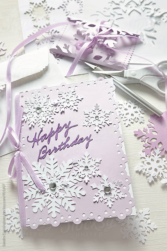 Closeup of a handmade birthday card with snowflakes  by Sandra Cunningham for Stocksy United