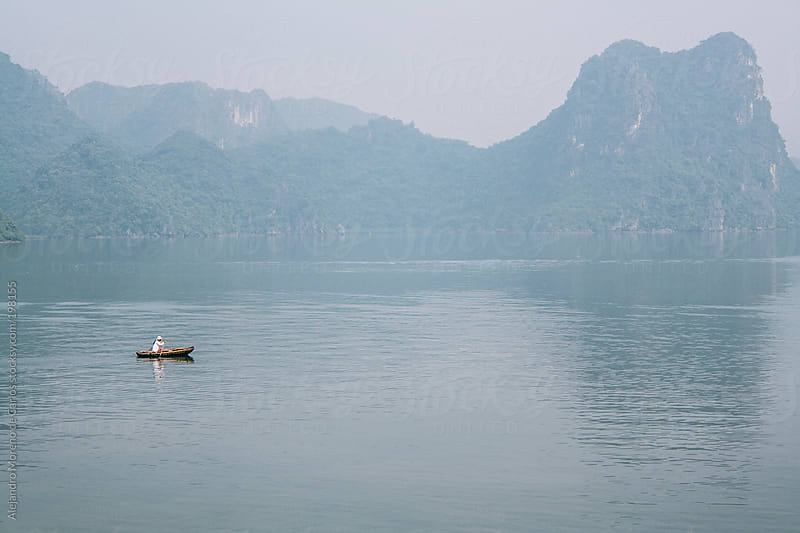 Woman on a rowing boat on sea with mist - Halong Bay, Vietnam, Asia by Alejandro Moreno de Carlos for Stocksy United