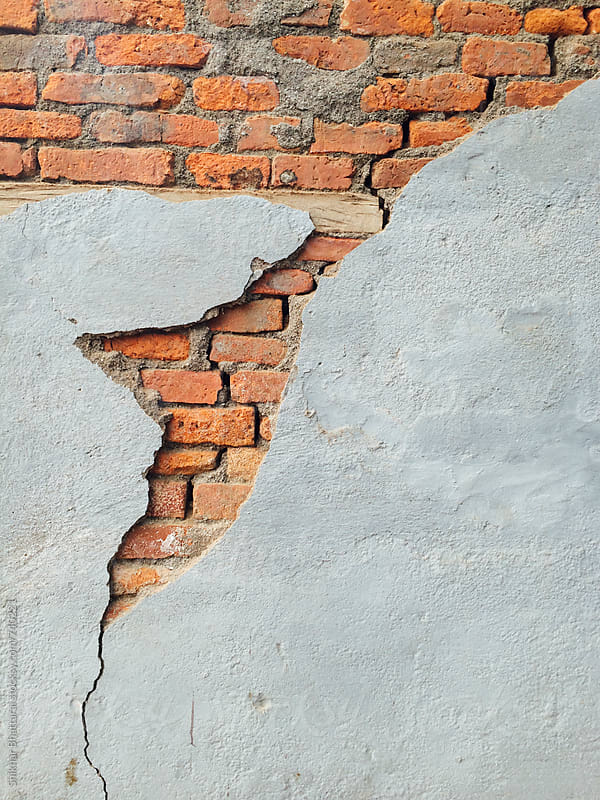 cracked cemented wall exposing the brick underneath. by Shikhar Bhattarai for Stocksy United