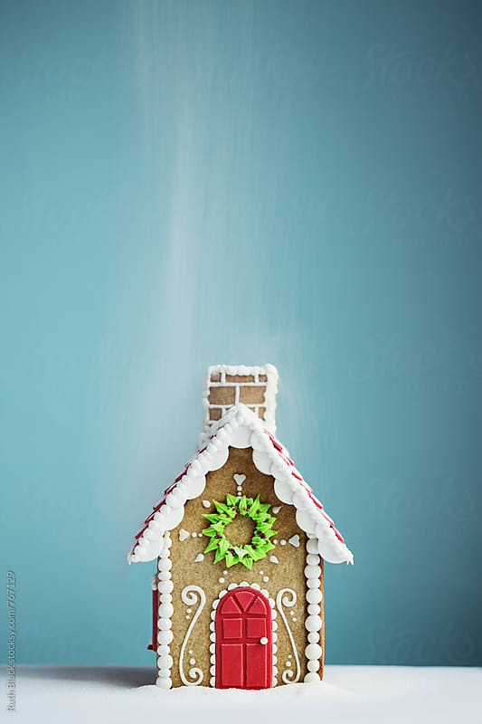 Gingerbread house in a sugar snow shower by Ruth Black for Stocksy United