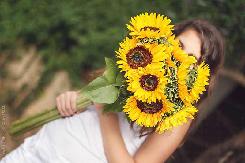 A young lady with a bouquet of sunflowers by Helen Sotiriadis for Stocksy United
