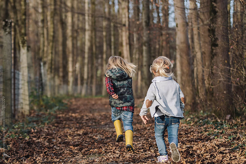 little boy and girl running in autumnal forest by Leander Nardin for Stocksy United