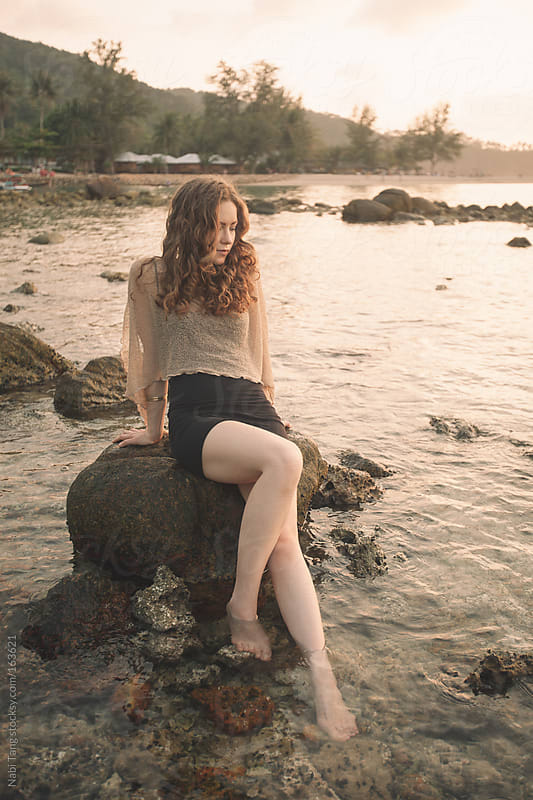 Young beautiful woman on the rocky beach by Nabi Tang for Stocksy United
