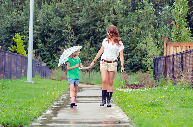 mother and daughter walking with umbrella by Tomas Kraus for Stocksy United