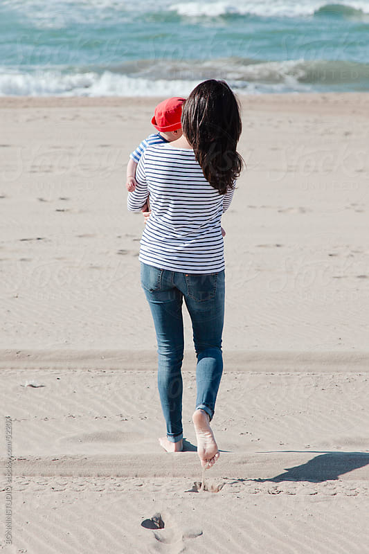 Mom with her baby walking on the beach by BONNINSTUDIO for Stocksy United