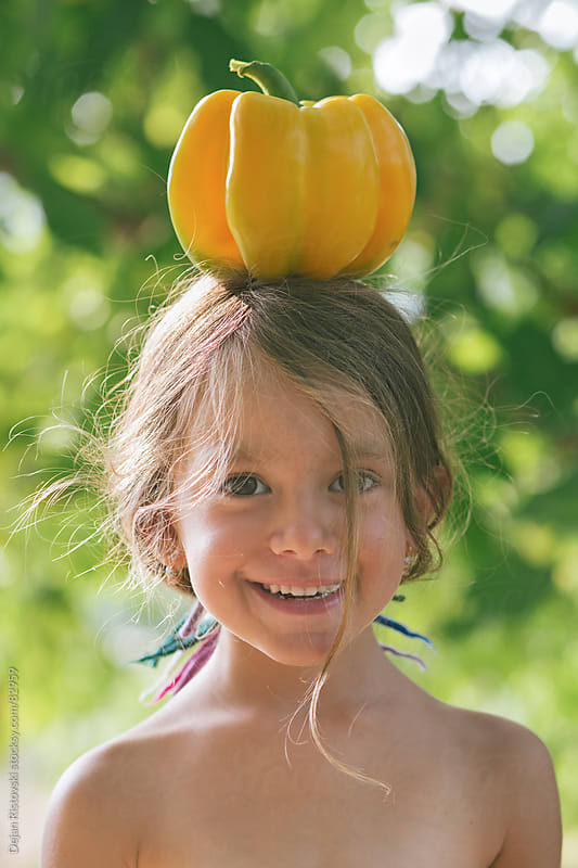 Child carrying yellow pepper on her head by Dejan Ristovski for Stocksy United