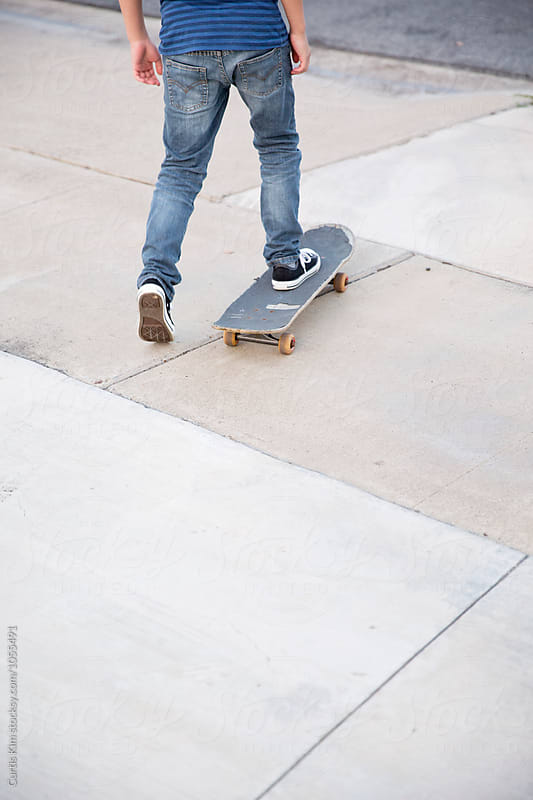 Kid riding his skateboard  by Curtis Kim for Stocksy United