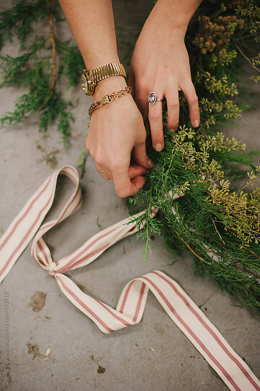 Female florist making festive holiday Christmas wreath with red striped ribbon by Daring Wanderer for Stocksy United