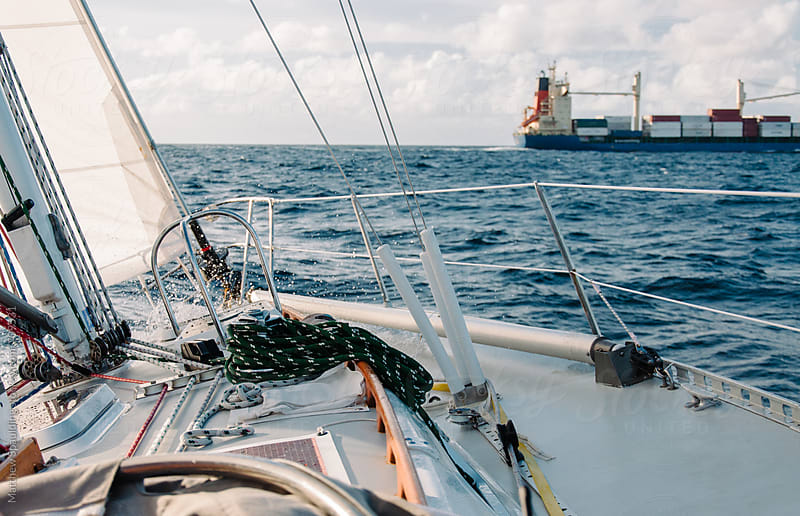 Bow of sailboat on ocean voyage passing shipping container by Matthew Spaulding for Stocksy United