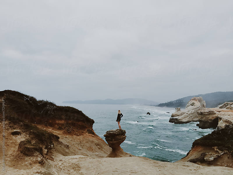 Standing on a rock at the coast by Dylan M Howell Photography for Stocksy United