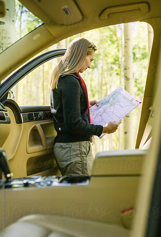 Woman Reading Map on Road Trip by Raymond Forbes LLC for Stocksy United