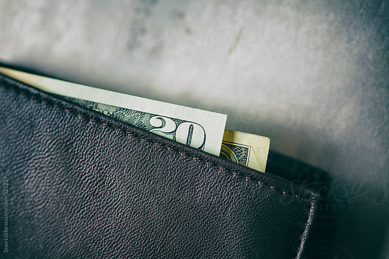 Wallet With Cash Peeking Out On Metal Background by Sean Locke for Stocksy United