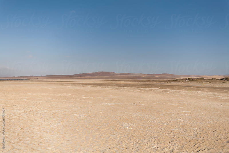 Desert location with barren hills in the distance by Ben Ryan for Stocksy United