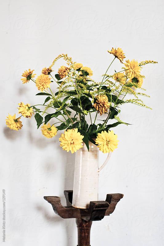 Wilting Yellow flowers in a vase by Melanie Kintz for Stocksy United