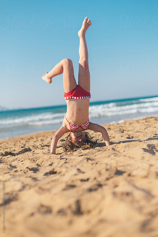 Child playing on the beach by Dejan Ristovski for Stocksy United