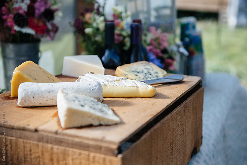 Variety of cheese displayed on an old wooden box at an outdoor party by Cara Dolan for Stocksy United