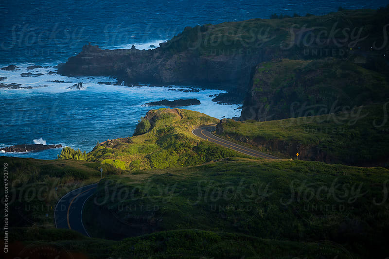 Curving Road in a beam of light overlooking the ocean by Christian Tisdale for Stocksy United