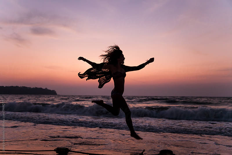 Carefree woman dancing in the sunset on the beach by Jovo Jovanovic for Stocksy United