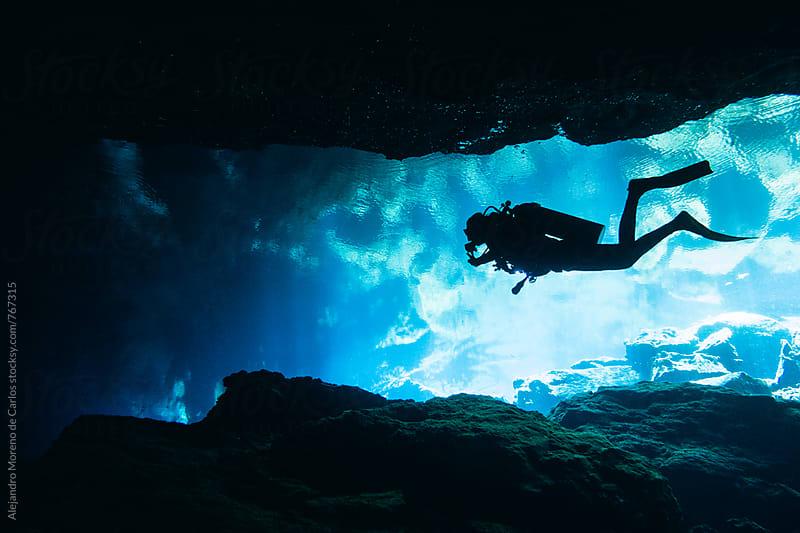 Silhouette of scuba diver doing cave diving in a cenote in Yucatán, Mexico by Alejandro Moreno de Carlos for Stocksy United