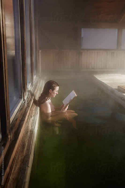 Woman reading book at Japanese Hot Springs by Trinette Reed for Stocksy United