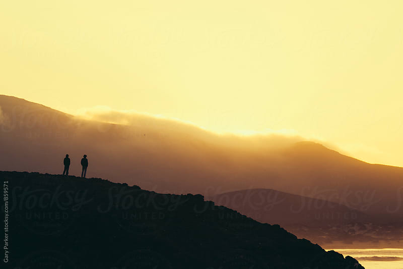 Two people stand on a hill overlooking the ocean as the sun rises by Gary Parker for Stocksy United