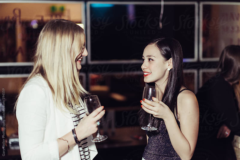 Young Women in Conversation at a Party or Bar by Gary Radler Photography for Stocksy United