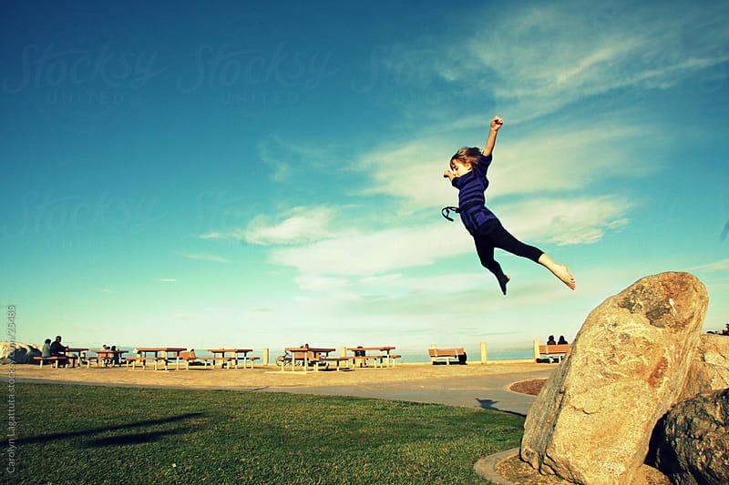 Girl jumping off a rock triumphantly - arms raised. by Carolyn Lagattuta for Stocksy United