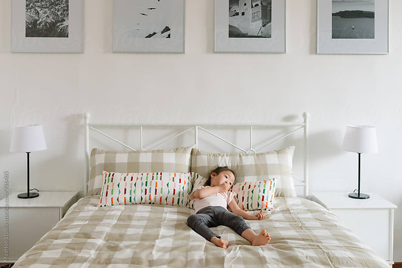 Adorable little  lying on bed by MaaHoo Studio for Stocksy United